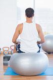 Man sitting on exercise ball