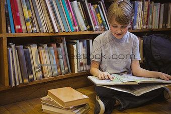 Little boy reading on library floor