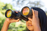 Cute little girl looking through binoculars