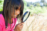 Cute little girl using magnifying glass in park