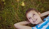 Cute little girl lying on grass