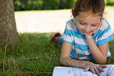 Cute little girl reading in park