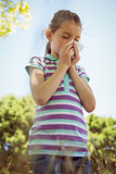 Cute little girl blowing her nose in park