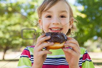 Little boy eating chocolate doughnut