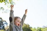 Cute little boy cheering in park