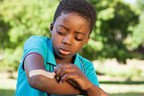 Little boy putting plaster on arm