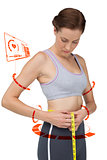Composite image of portrait of a fit woman measuring waist