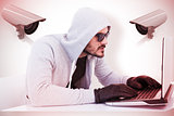 Composite image of serious burglar hacking into laptop