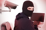 Composite image of hacker sitting and hacking laptop