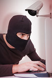 Composite image of focused burglar hacking into laptop