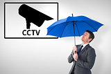 Composite image of businessman sheltering under blue umbrella