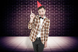 Composite image of geeky hipster in party hat
