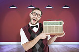 Composite image of geeky hipster holding a retro radio