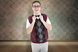Composite image of geeky hipster fixing his bow tie