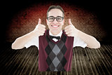 Composite image of smiling geeky hipster looking at camera showing thumbs up