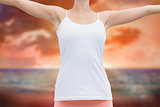 Composite image of beautiful woman with arms raised against the sky