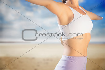 Composite image of sporty blonde standing on the beach with arms out