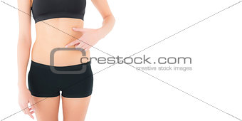 Closeup mid section of a fit woman with hand on stomach