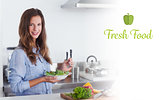 Fresh food against woman in the kitchen holding a salad bowl with lettuce