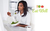 Eat well against pretty businesswoman eating a salad at her desk