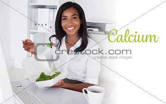 Calcium against smiling businesswoman eating a salad at her desk