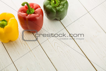 Three peppers on chopping board