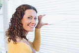 Curious woman looking through blinds