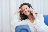 Smiling woman sitting on the couch and speaking on the phone