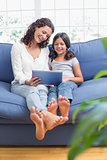 Happy mother and daughter sitting on the couch and using tablet