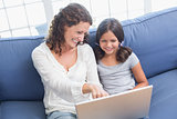 Happy mother and daughter sitting on the couch and using laptop