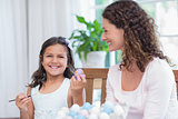 Happy mother and daughter painting easter eggs