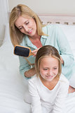 Smiling mother brushing her daughters hair