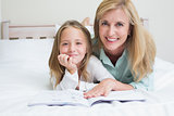 Happy mother and daughter reading a book