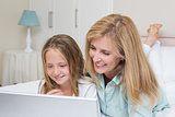 Happy mother and daughter using laptop