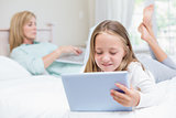 Mother using laptop while daughter using tablet pc on the bed