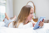Little girl using tablet pc in the bed