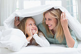 Mother and daughter looking at each other under the duvet