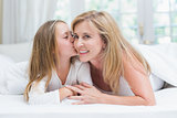 Daughter kissing her mother on the cheek in the bed