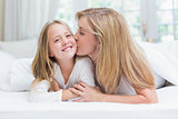 Mother kissing her daughter on the cheek in the bed