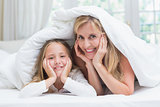 Mother and daughter looking at camera under the duvet