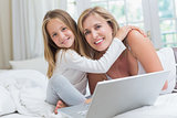 Mother and daughter using laptop in the bed