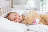 Little girl lying in her bed holding her teddy