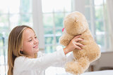 Happy little girl holding her teddy