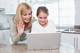 Mother and daughter talking with someone with the laptop