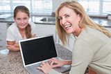 Happy mother using laptop with her daughter