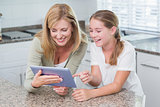 Happy mother and daughter using tablet pc together