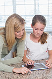Mother and daughter using tablet pc together