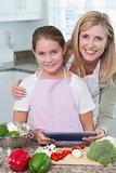 Mother and daughter cooking together with tablet pc