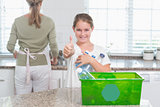 Little girl holding recycling bottles with thumbs up