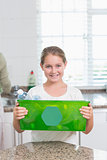 Happy little girl holding recycling box